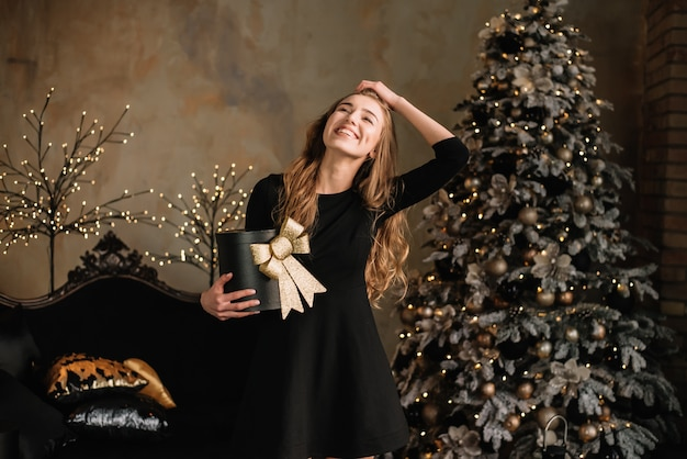 Donna allegra della donna che tiene una scatola con i regali vicino all'albero di natale