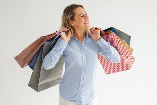 Donna allegra godendo lo shopping e portando molte borse
