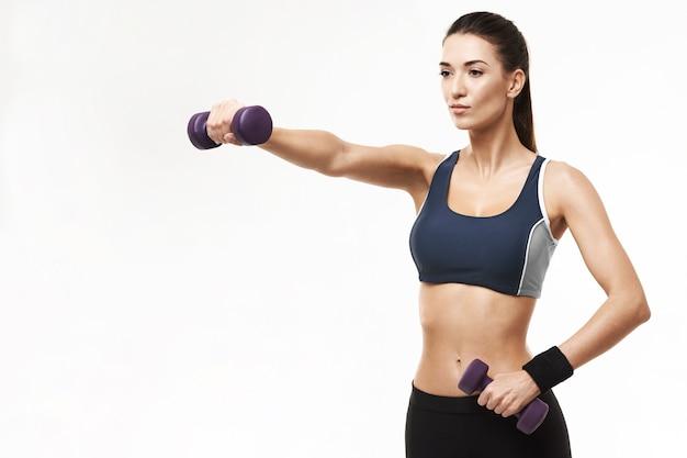 Donna allegra in armi di addestramento degli abiti sportivi con le teste di legno su bianco.