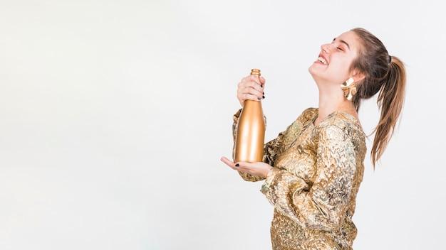 Donna allegra in piedi con una bottiglia di champagne