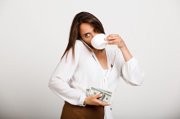 Donna allegra moda, bere un caffè, tenere soldi e parlare al telefono