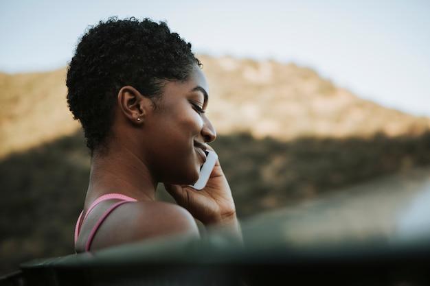 Donna allegra parlando al telefono