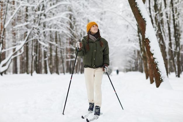 Donna allegra sci nella foresta