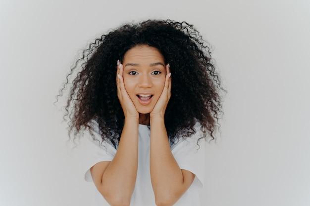 Donna allegra sorpresa con taglio di capelli afro, tiene entrambe le mani sulle guance