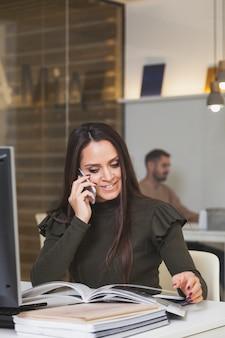 Donna allegra sul telefono che guarda rivista