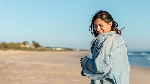 Donna allegra sulla spiaggia che osserva sopra la spalla