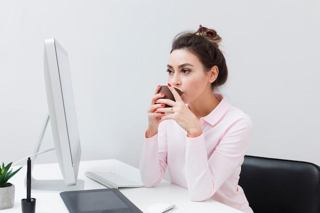 Donna allo scrittorio che beve caffè e che esamina computer