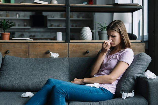 Donna ammalata che si siede sul sofà che soffia il suo naso
