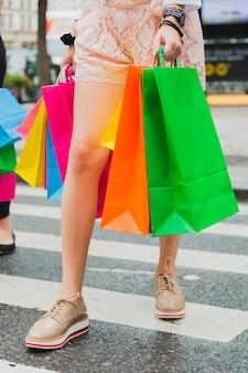 Donna andando sulla strada con borse della spesa