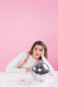 Donna annoiata che si siede alla tavola con palla da discoteca lucida