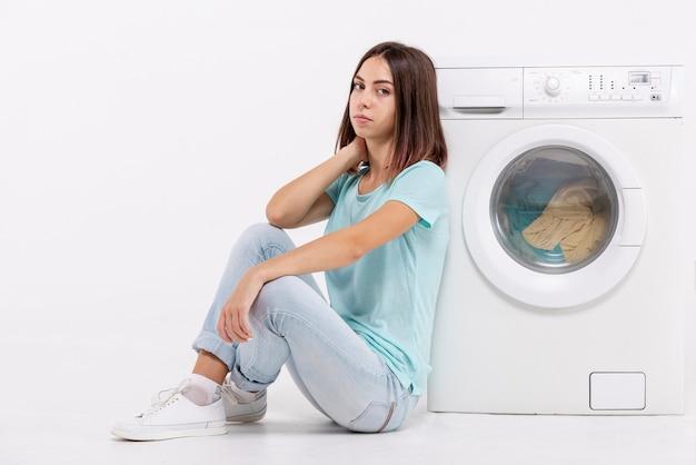 Donna annoiata della foto a figura intera che si siede vicino alla lavatrice