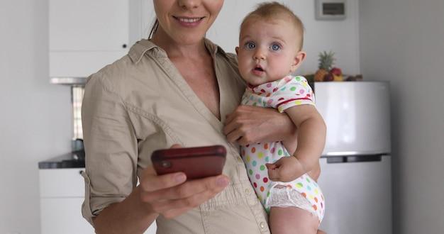 Donna anonima che sorride e che passa in rassegna smartphone mentre stando nella cucina e tenente dolce bambino