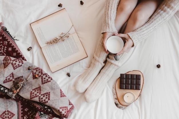 Donna anonima con latte rilassante sul letto