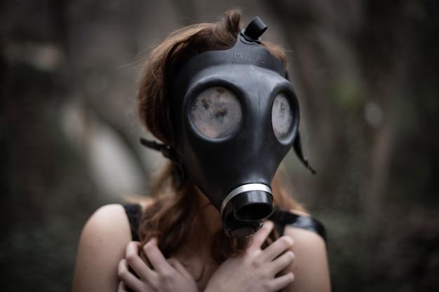 Donna anonima in abiti neri e maschera antigas nella straordinaria foresta spettrale
