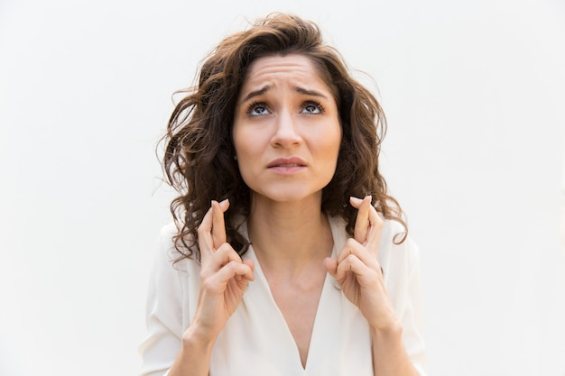 Donna ansiosa tenendo le dita incrociate e pregando