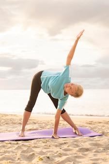Donna anziana a praticare yoga sulla spiaggia