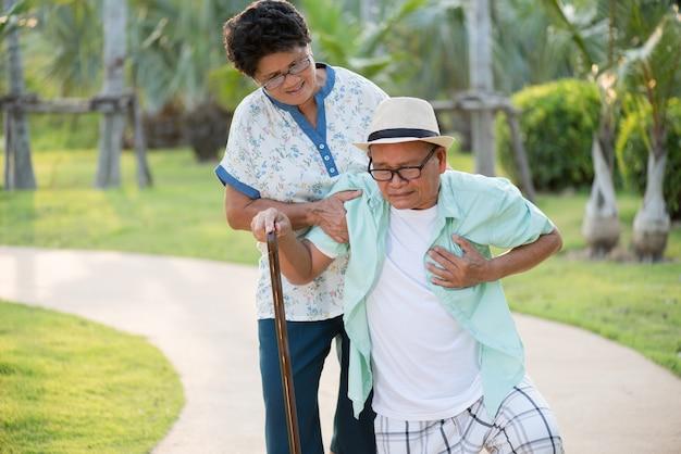 Donna anziana asiatica che aiuta un uomo anziano che ha un dolore al cuore, attacco di cuore