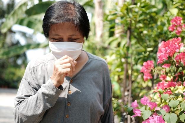 Donna anziana asiatica che indossa una maschera di stoffa bianca per prevenire il virus covid-19 o corona e tossire in thailandia e protezione per l'inquinamento atmosferico valore 2.5. salute e medicina del conconcept anziano
