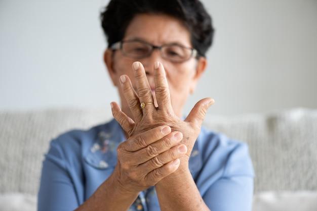 Donna anziana asiatica che si siede sul sofà e che ha dolore della mano