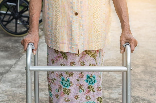 Donna anziana asiatica che sta con le sue mani su un bastone da passeggio