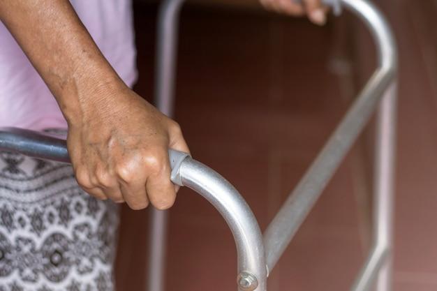Donna anziana asiatica che sta con le sue mani su un supporto del camminatore