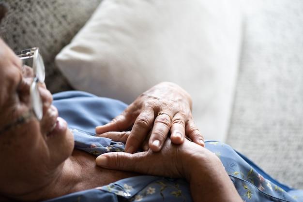 Donna anziana asiatica malata che si trova sul sofà e che ha un dolore sul cuore