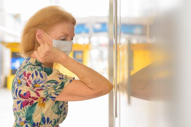 Donna anziana bionda con maschera che preme il pulsante dell'ascensore con il gomito per evitare di diffondere il coronavirus covid-19