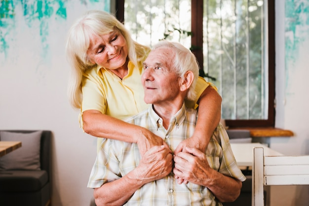 Donna anziana che abbraccia uomo anziano seduto a casa