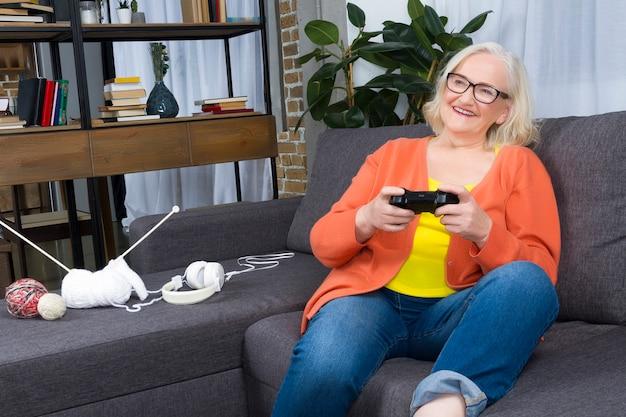 Donna anziana che gioca la stazione di gioco con i rilievi di gioia