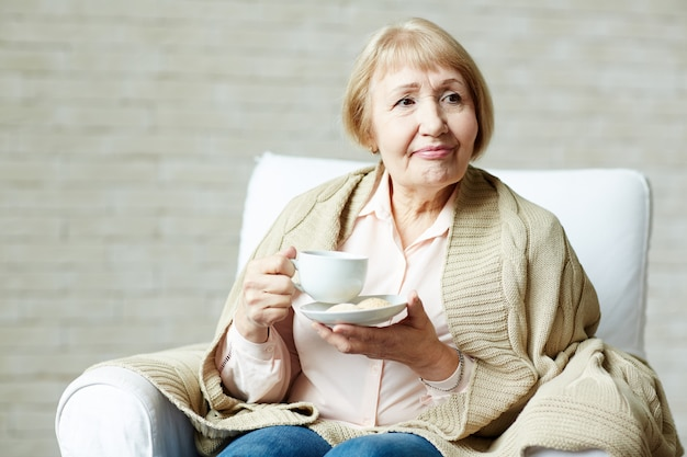 Donna anziana che gode del tè