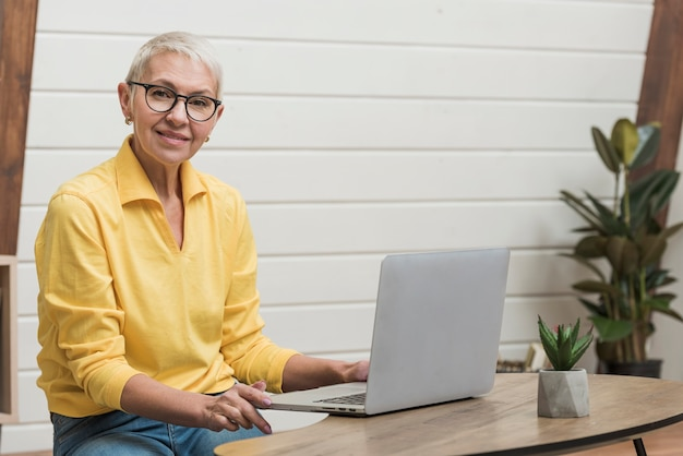 Donna anziana che guarda attraverso internet sul suo computer portatile