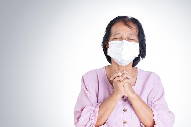 Donna anziana che indossa maschere, che copre la bocca e il naso, prevenendo il coronavirus o covid-19.