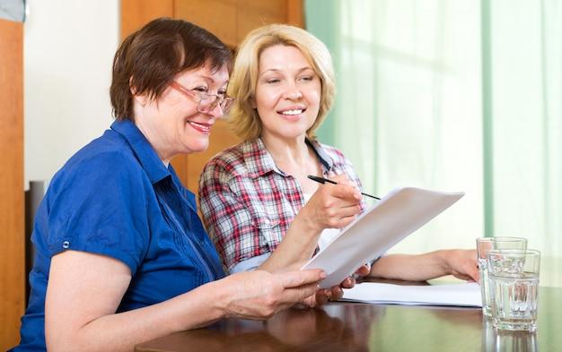 Donna anziana che lavora con i contratti
