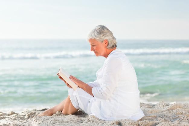 Donna anziana che legge il suo libro sulla spiaggia
