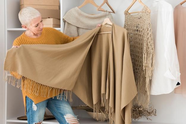 Donna anziana che mostra i suoi vestiti