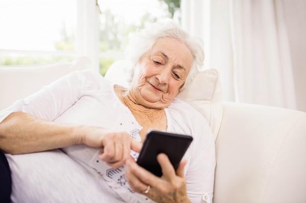 Donna anziana che per mezzo del suo smartphone che si trova sul sofà