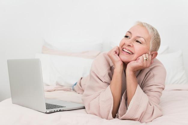 Donna anziana che posa in accappatoio con il computer portatile a letto
