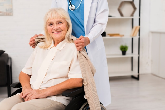 Donna anziana che posa in sedia a rotelle
