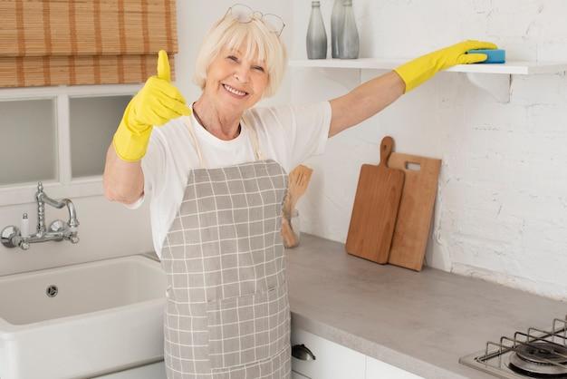 Donna anziana che pulisce la cucina con i guanti