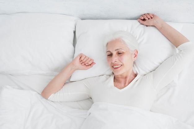 Donna anziana che si sveglia nel letto