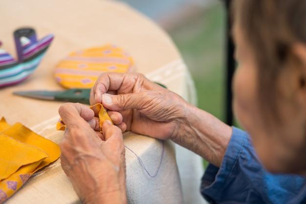 Donna anziana con caregiver nella terapia occupazionale dei mestieri dell'ago per l'alzheimer o la demenza