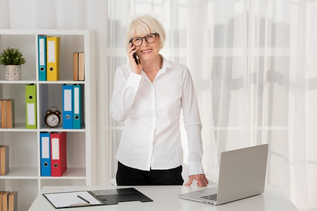 Donna anziana con gli occhiali che parla al telefono