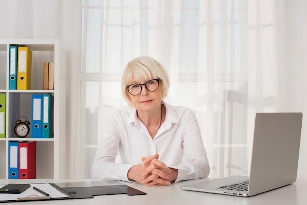 Donna anziana con gli occhiali che si siedono nel suo ufficio