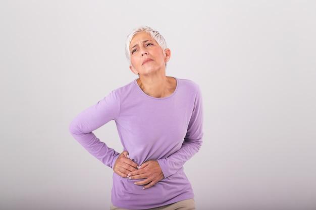 Donna anziana con i capelli grigi che tocca la sua anca dolorante. sconvolta la donna anziana matura che tocca la schiena si sente ferita osteoartrite reni dolori muscolari doloranti