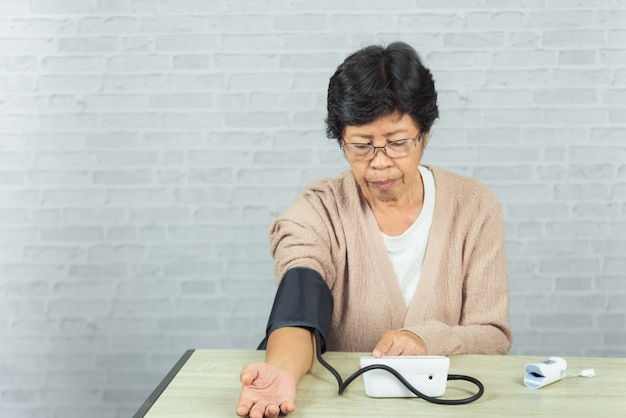 Donna anziana con manometro che controlla il livello di pressione sanguigna sul tavolo