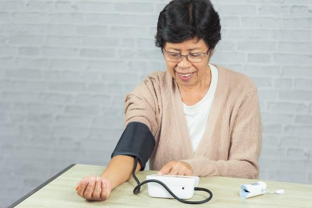 Donna anziana con tonometro che controlla il livello di pressione sanguigna