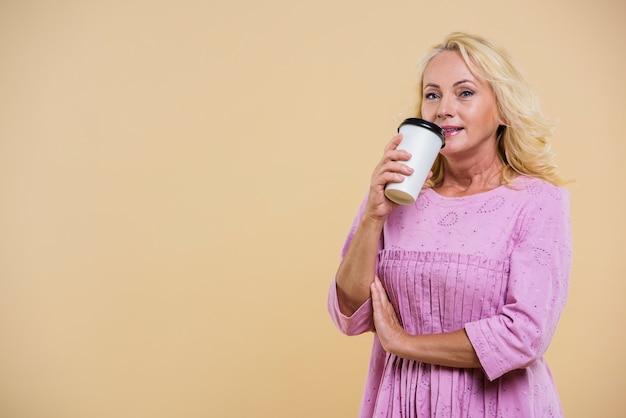 Donna anziana con una tazza di caffè guardando la telecamera