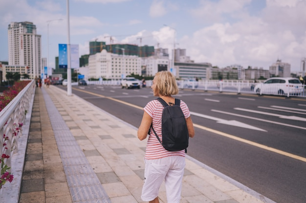 Donna anziana con zaino e sacco a pelo del viaggiatore che cammina nella città asiatica del centro con i grattacieli. natura di avventura di viaggio in cina, bella destinazione turistica asia, concetto di viaggio di viaggio di vacanze estive di vacanza