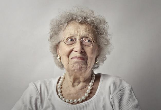 Donna anziana contro un muro bianco con uno sguardo preoccupato sul viso