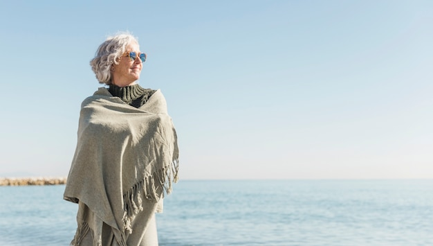 Donna anziana del colpo medio che osserva via